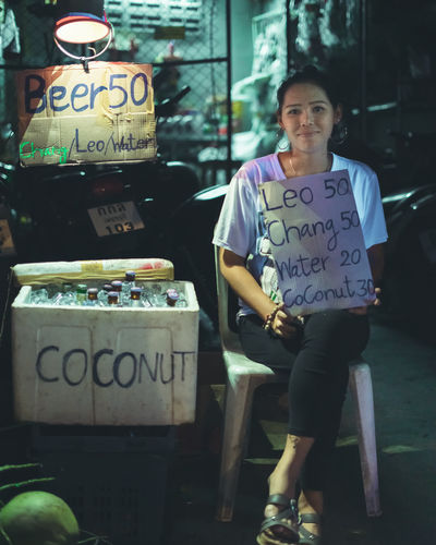 Small Business Seller Advertising her products Message Looking At Camera Food And Drink Portrait Sign Script Real People Communication Western Script Text Front View Focus On Foreground Illuminated Handwriting  Beer Coconut Seller Small Business Sitting Outside DIM Watermelon Sign Signs Signboard One Person