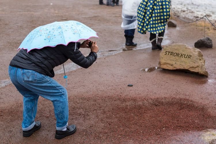 Street Photography Streetphotography Man Tourist Attraction  Tourist Geysir Strokkur Iceland Men Real People Day People Casual Clothing Childhood Street Full Length Standing City Low Section Wet Protection Lifestyles Umbrella Leisure Activity Occupation Two People This Is Aging The Traveler - 2018 EyeEm Awards The Street Photographer - 2018 EyeEm Awards 2018 In One Photograph