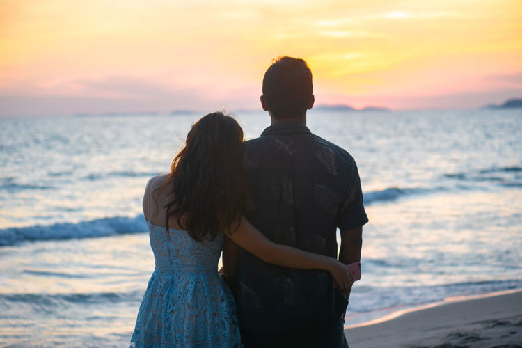 Rear view of couple standing at beach during sunset