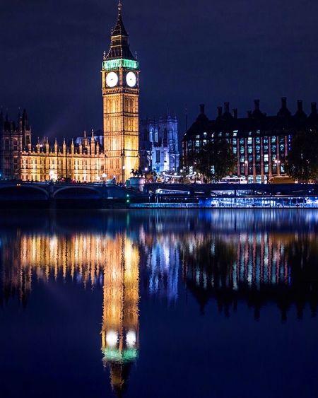 Illuminated big ben by thames river at night