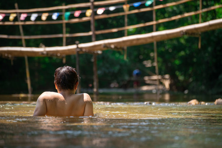 One Person Shirtless Rear View Real People Men Headshot Water Lifestyles Child Leisure Activity Childhood Portrait Boys Males  Selective Focus Built Structure Day Focus On Foreground Outdoors