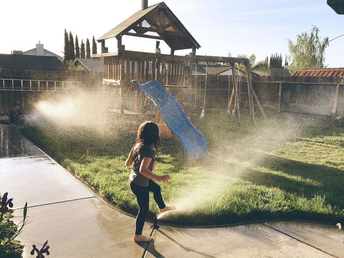 Boy playing in water against sky