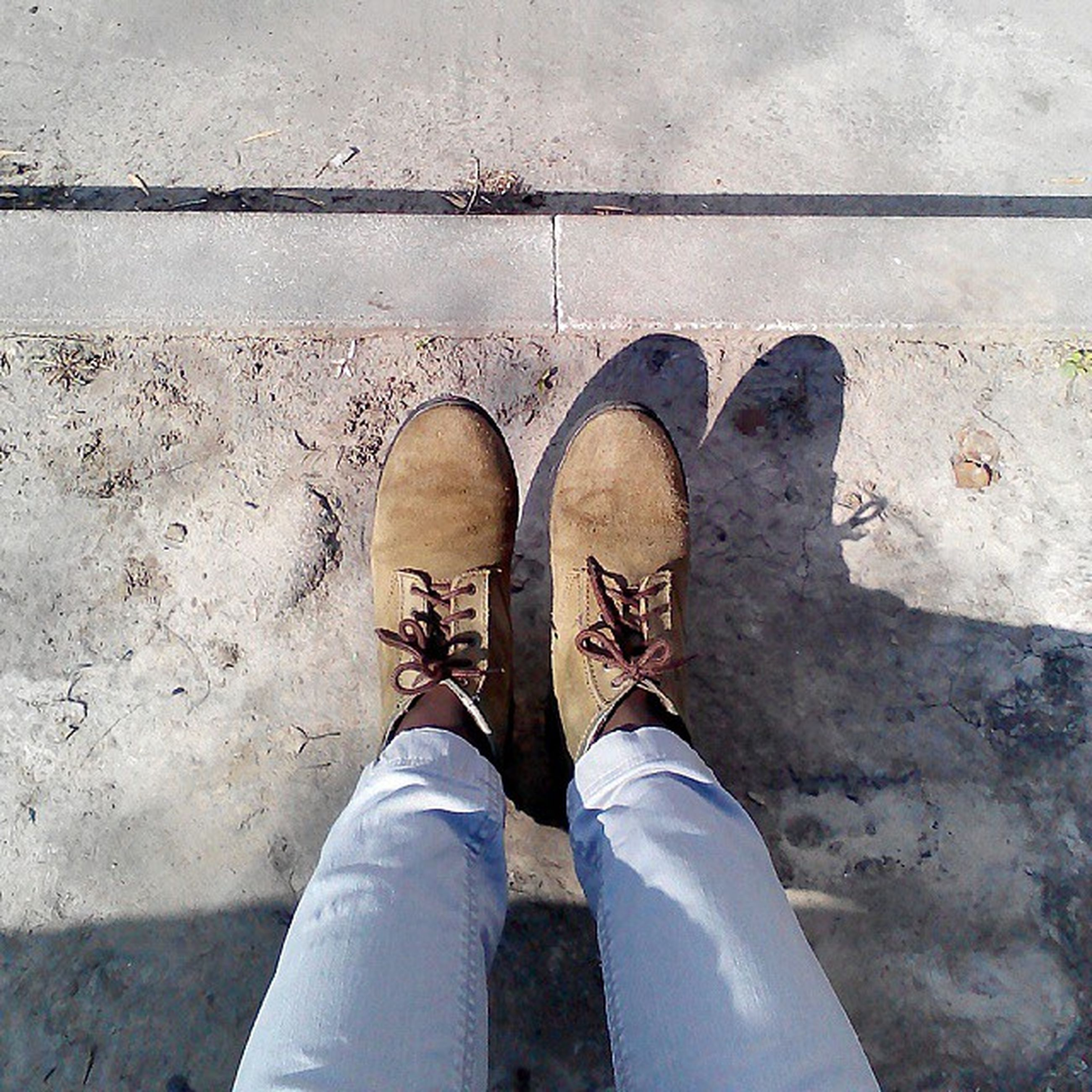 low section, person, shoe, personal perspective, footwear, human foot, standing, high angle view, jeans, men, part of, lifestyles, unrecognizable person, street, directly above, day, outdoors