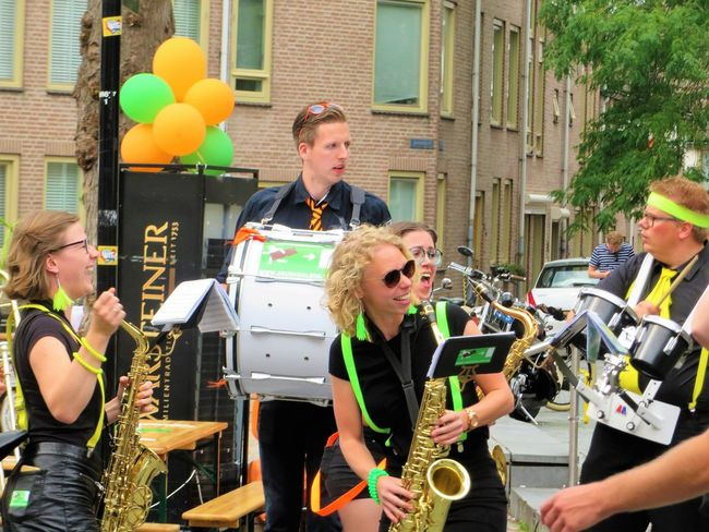 Architecture Balloon Blond Hair Building Exterior Built Structure City Day Holding Leisure Activity Lifestyles Men Mid Adult Mid Adult Men Music Musical Instrument Musician Occupation Outdoors Real People Saxophone Standing Togetherness Young Adult Young Men Young Women