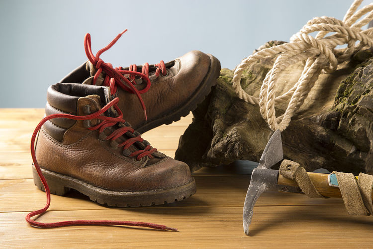 Close-up of shoes with equipment on wooden table