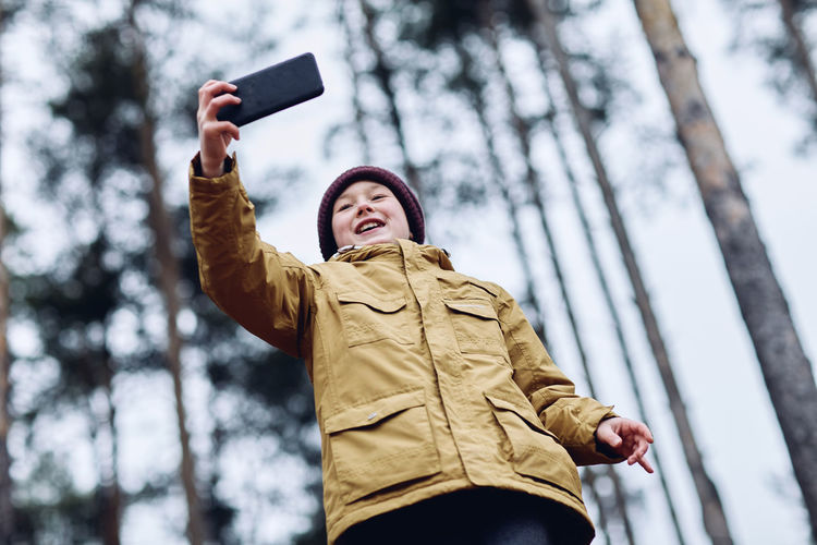 Low angle view of young woman using mobile phone in winter