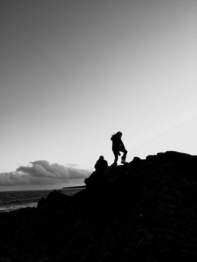 Silhouette people on rock on land against sky