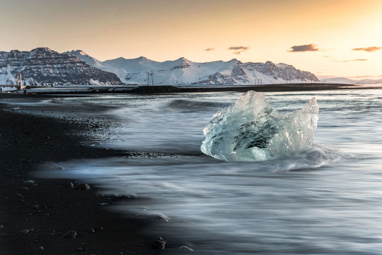 Scenic view of ice berg in sea against sky during sunset