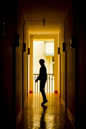 Full Length Of Silhouette Person Standing In Corridor