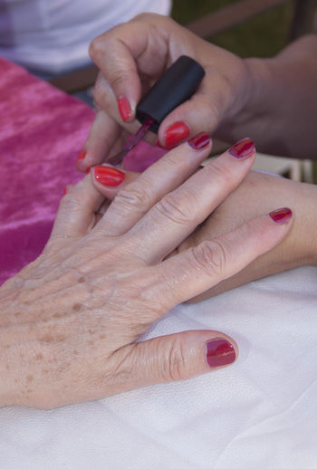 Cropped Hands Of Beautician Painting Fingernails
