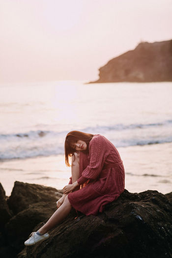 Portrait Of Woman Sitting On Rock At Beach Against Sky
