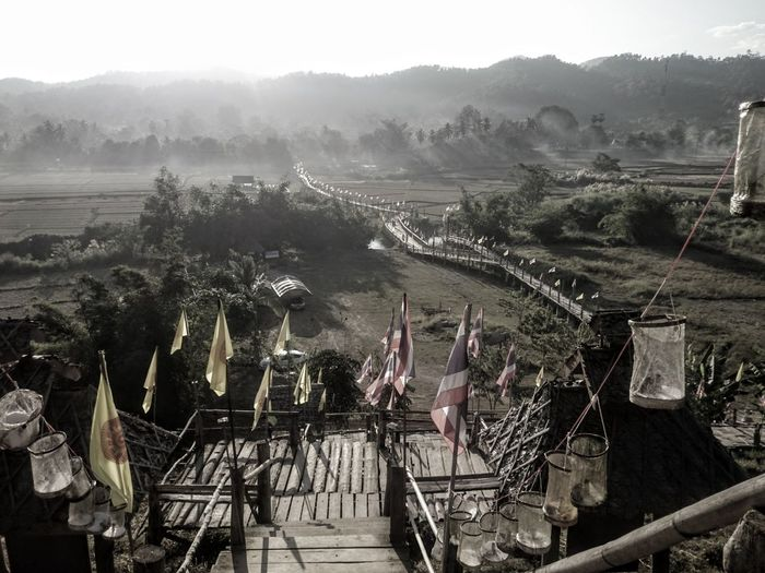 Flags on footbridge against landscape