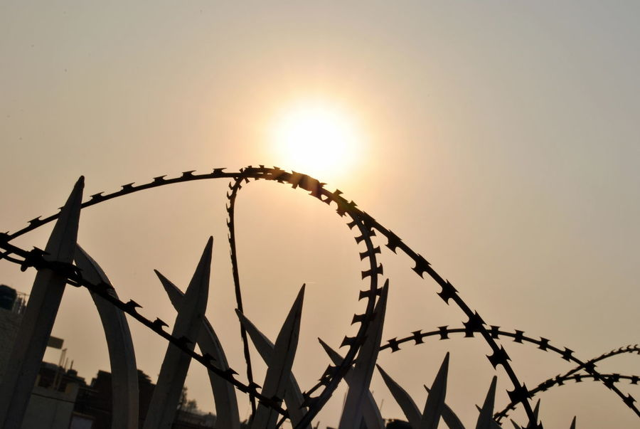 Fences!! Amusement Park Barbed Wire Boundary Closed Day Dramatic Sky Fence Metal Minimalism No Entry No People Non-urban Scene Orange Color Outdoors Polluted Sky Sepia Shadow Silhouette Sky SP Summer Sunny Day Sunset Urban Warm