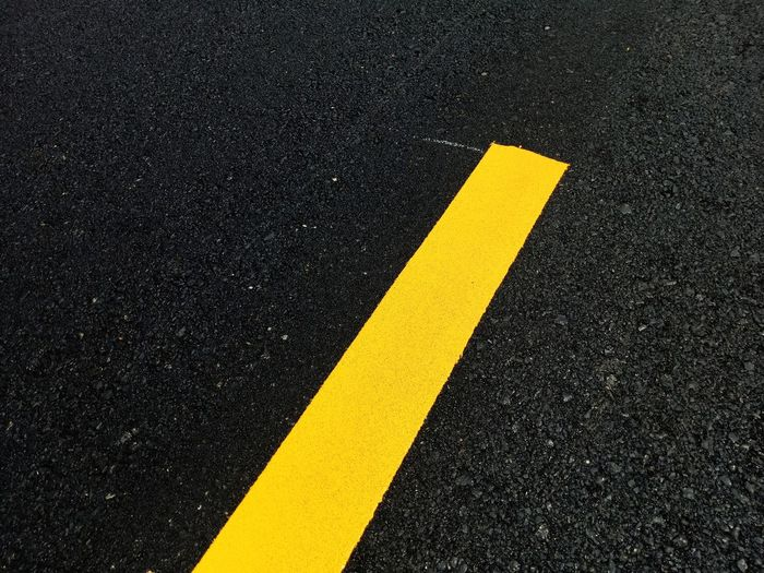 Yellow Road Sign Asphalt Transportation Symbol Marking Communication Road Marking City No People Street High Angle View Direction Guidance Close-up Black Color Arrow Symbol Outdoors Single Line Dividing Line