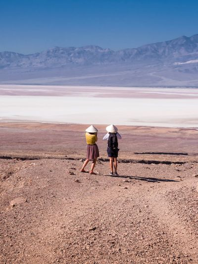 Rear view of friends standing in desert against mountains