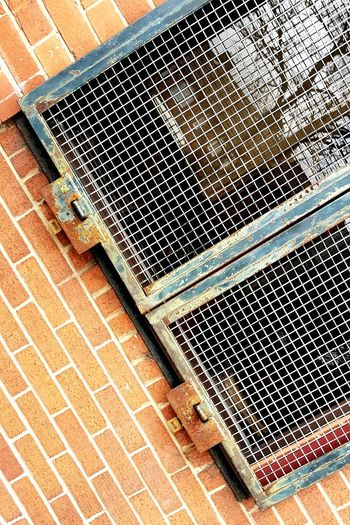 High angle view of metal grate on footpath