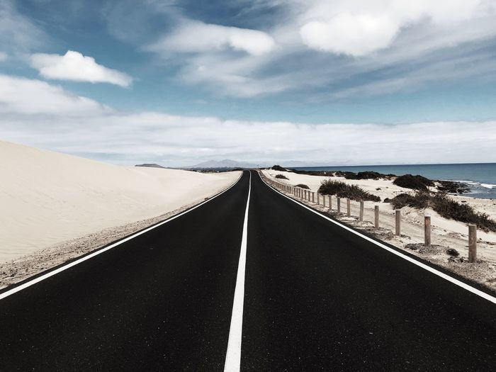 Diminishing perspective of country road by sea against cloudy sky
