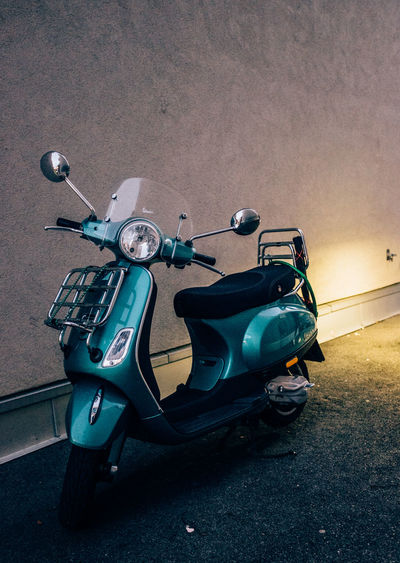 Vintage scooter parked by wall on street