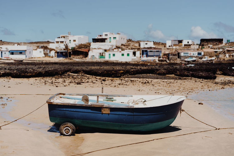 Small fishing boat in blue color standing on the sandy beach with local village houses in the background. Shot in Fuerteventura. Sea Boat Sunny Nature Ocean Island Water Beautiful Small Old Adventure Shore Fisherman Boat Coastline Outdoors Life Blue Sand Landscape Beach Fiberglass Fishing Local Fisher Fishermen Fisherman Tiny Fuerteventura Low Tide Village Atlantic Vintage Rural Canary Islands Traditional Lifestyle Transportation Standing Lagoon Postcard Moment Nautical Vessel Fishing Boat