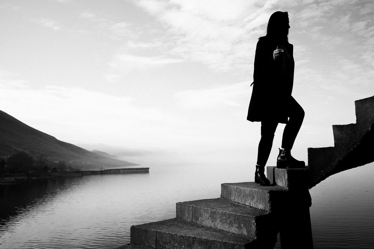 Silhouette of woman standing on steps against lake