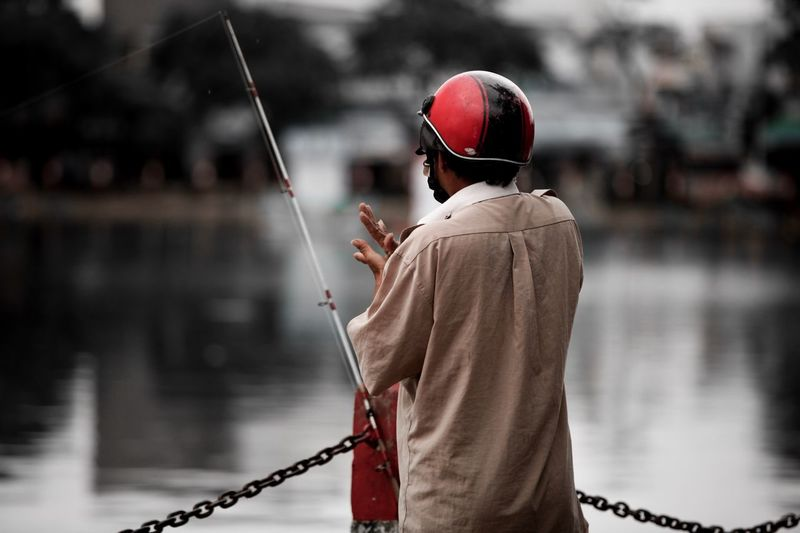 motorcyclist with fishing rod, Can Tho, Vietnam Helmet Vietnam Can Tho Focus On Foreground Real People Water One Person Rear View Men Day Fishing Lifestyles Standing Holding Outdoors Waist Up