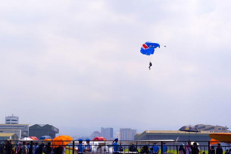 Man paragliding against cloudy sky