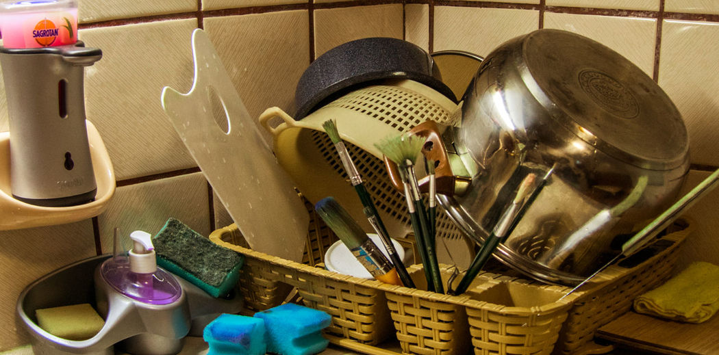 Paintbrushes And Kitchen Utensils In Basket At Home