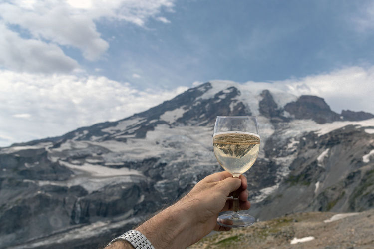 Cropped image of man hand holding wineglass against snowcapped mountain