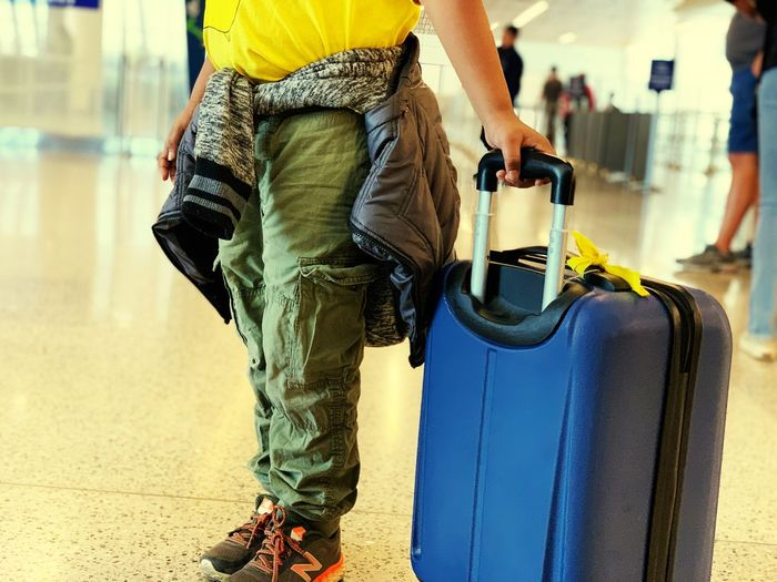 Unaccompanied minor traveling at airport young traveler Casual Clothing Real People Focus On Foreground One Person Men Bag Travel Carrying Standing Outdoors Day Transportation Rear View Midsection City Incidental People Holding Luggage City Life Jeans