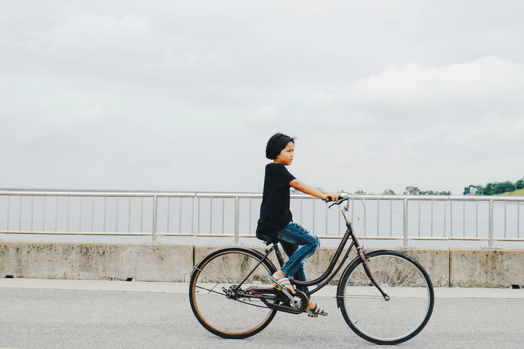 Man riding bicycle on railing against sky
