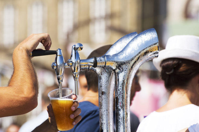 Close-up of man filling alcohol in glass from beer tap