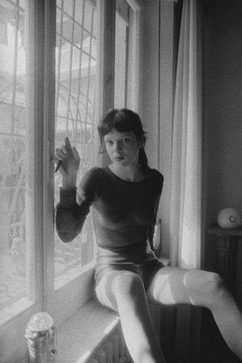 Portrait of young woman sitting on window at home