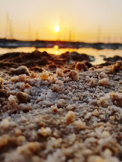 Surface level of beach against sky during sunset