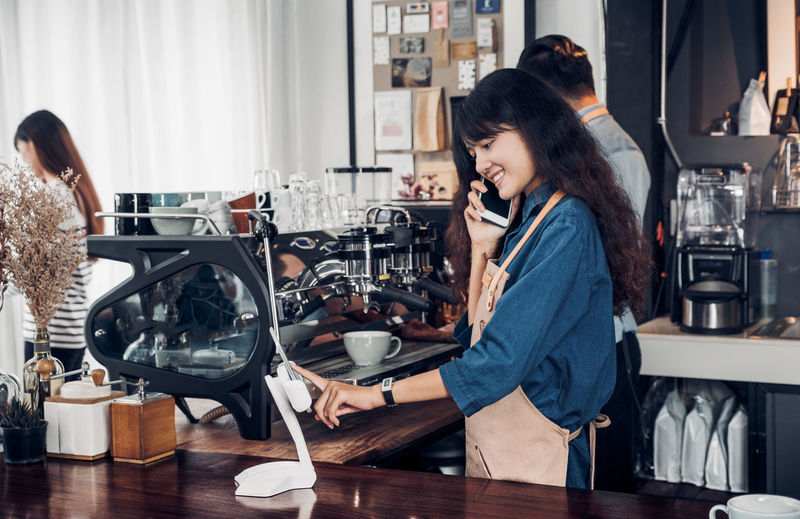 Smiling barista talking on mobile phone in cafe