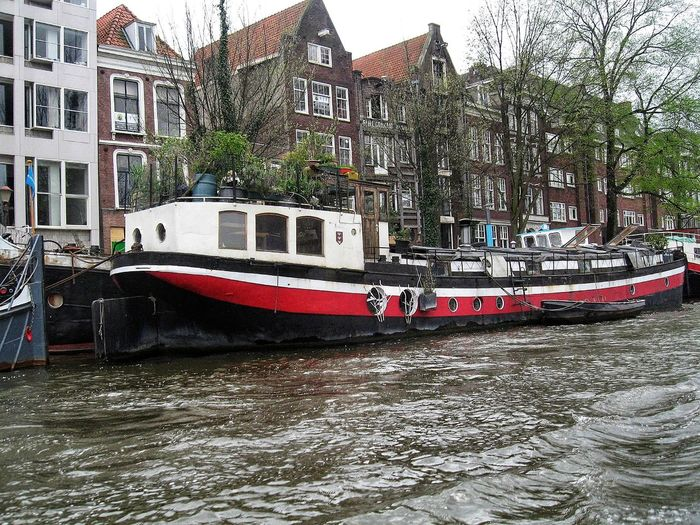 Boat moored on river by buildings in city
