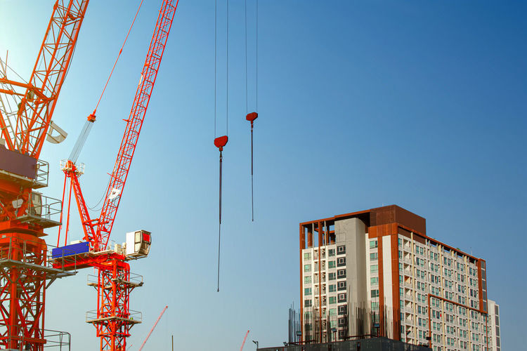 Low angle view of cranes against buildings against clear blue sky