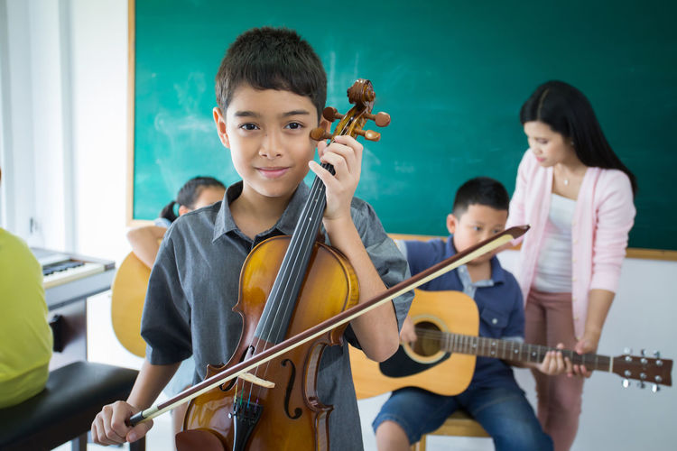 Portrait Of Boy Playing Violin In Classroom
