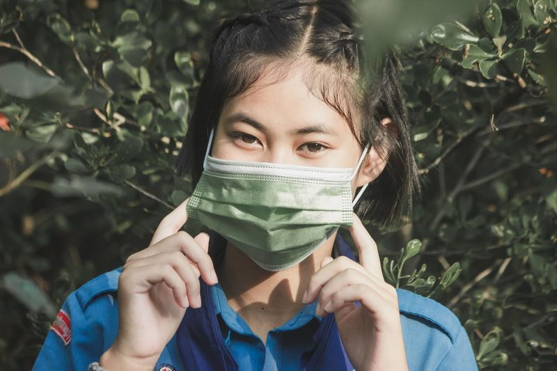Portrait of young woman wearing face mask the item amid coronavirus pandemic
