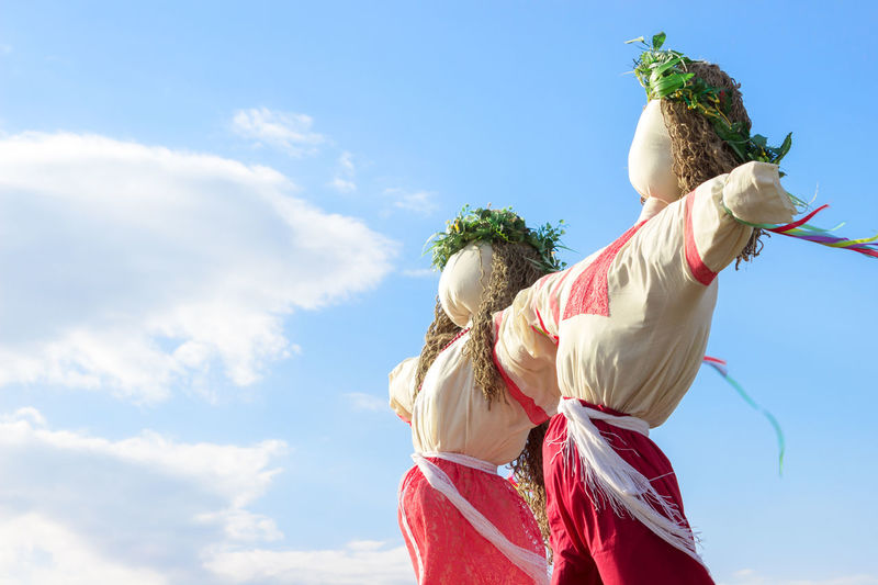 Low angle view of scarecrows against sky