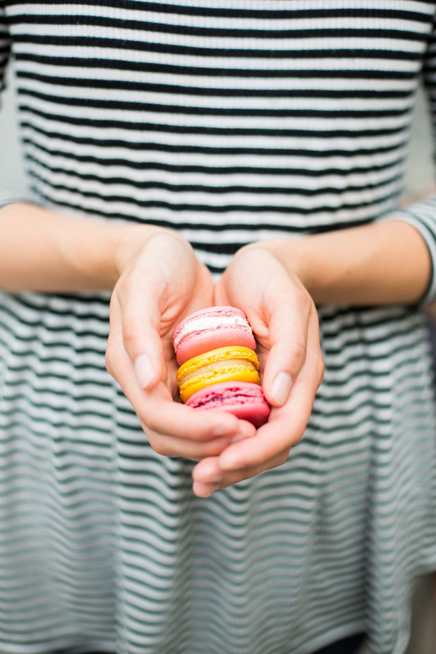 Midsection Of Woman Holding Colorful Macaroons