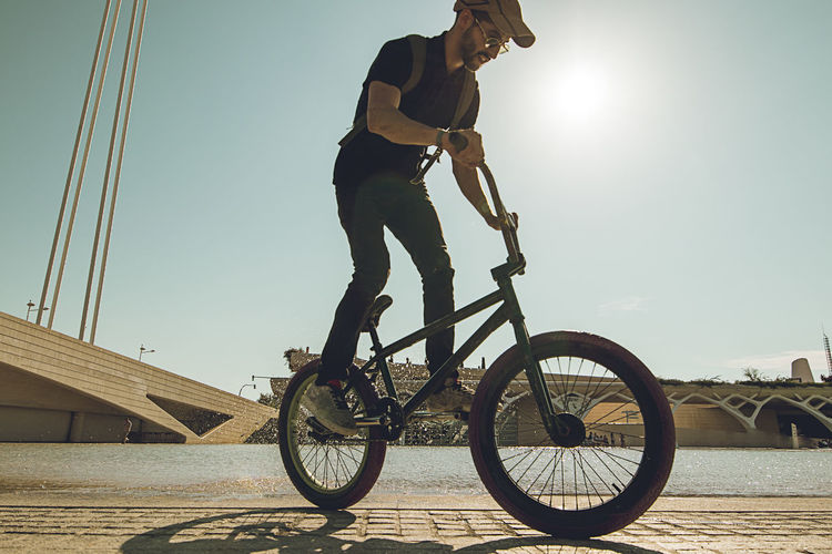 Low angle view of man riding bicycle against clear sky