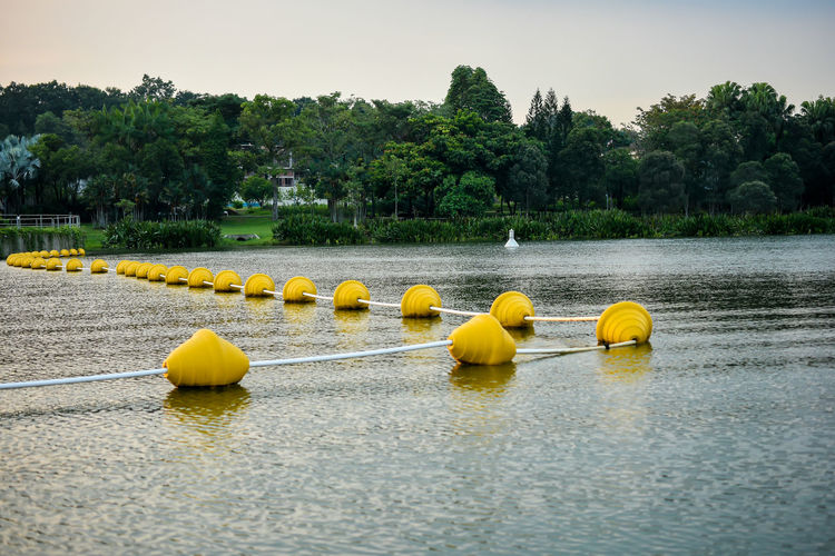 Buoyancy barrier Barrier Beauty In Nature Buoy Buoyancy Balls Day Lake Nature No People Outdoors Scenics Sky Tranquil Scene Tranquility Tree Water Yellow