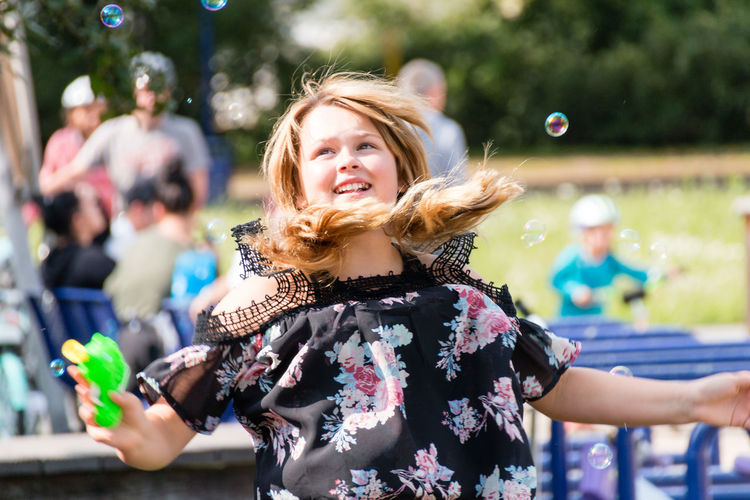 Woman playing amidst bubbles at park
