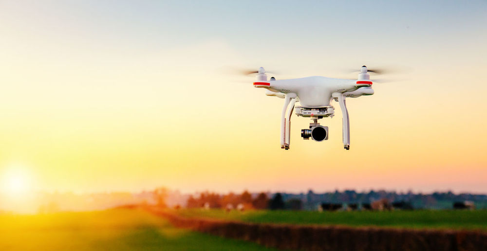 Quadcopter flying over field against sky during sunset