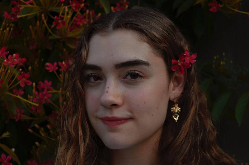 Close-up portrait of beautiful young woman against flowering plants