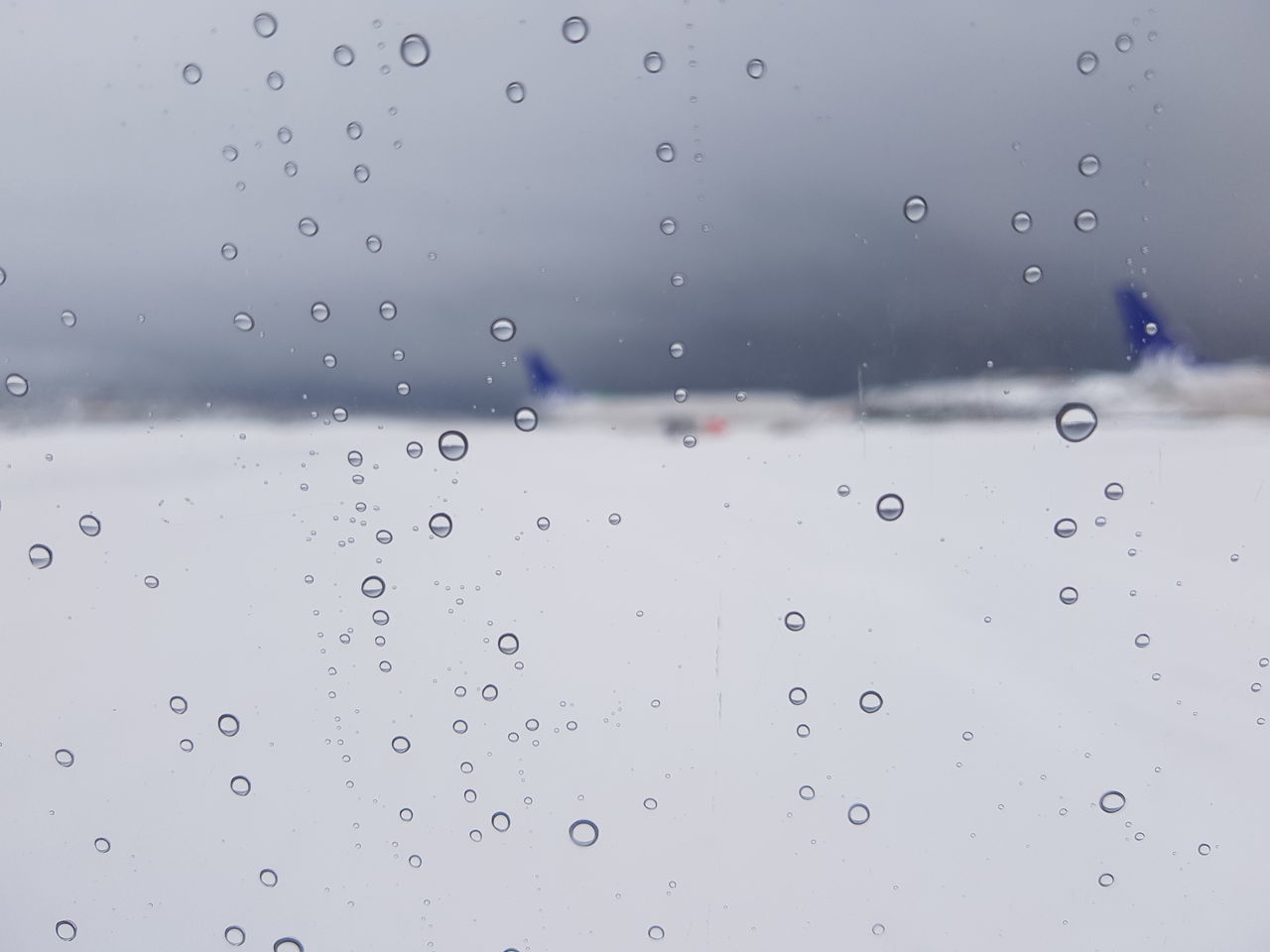 drop, water, wet, glass - material, window, rain, transparent, no people, close-up, indoors, airplane, nature, backgrounds, focus on foreground, air vehicle, raindrop, transportation, full frame, rainy season, glass, purity