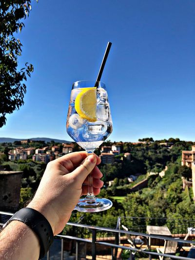Cropped hand holding drink against clear blue sky