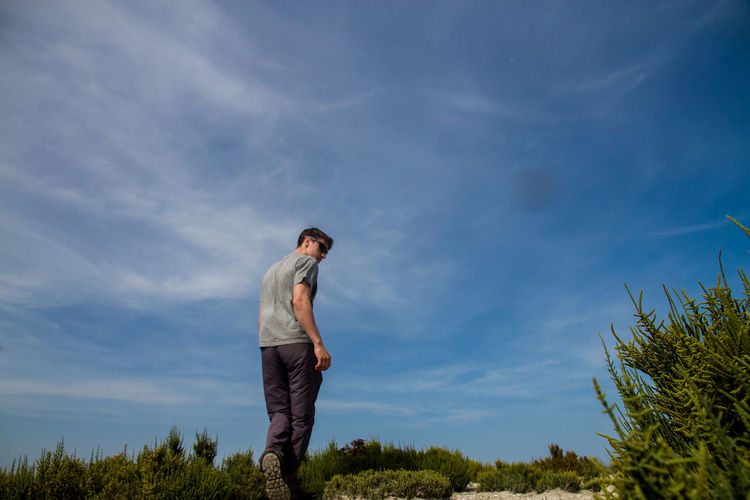 Low angle view of man standing on field against sky