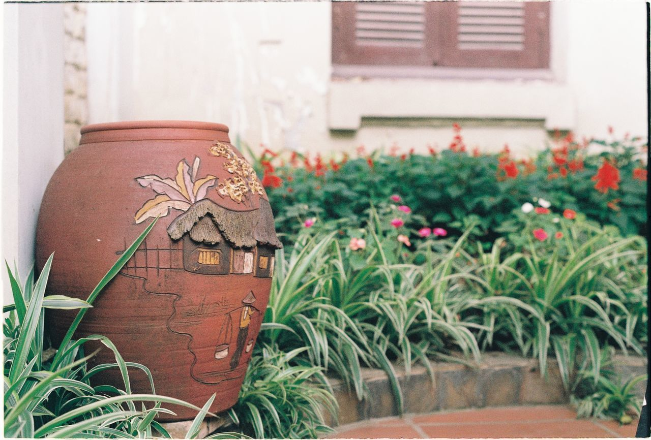 plant, no people, growth, nature, potted plant, decoration, day, flower, art and craft, architecture, flowering plant, built structure, plant part, leaf, outdoors, close-up, focus on foreground, green color, creativity, building exterior, flower pot, ornate