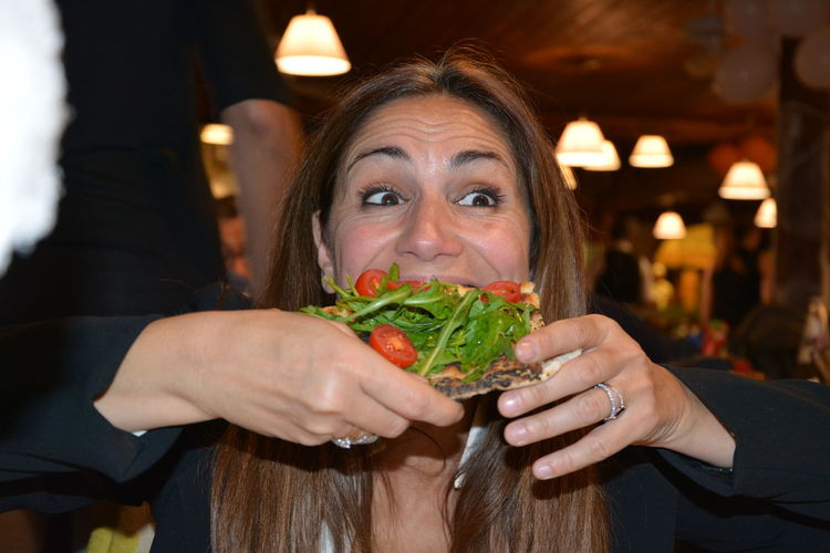 Close-up of woman eating open sandwich in restaurant